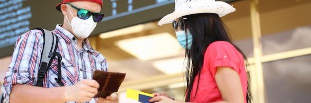 Hombre y mujer tienen pasaporte con retrato de billete de avión. viaje después del concepto covid-19