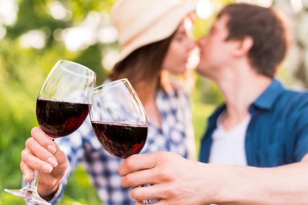 Hombre y mujer tintineando copas con vino