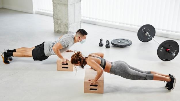 Hombre y mujer de tiro completo haciendo flexiones