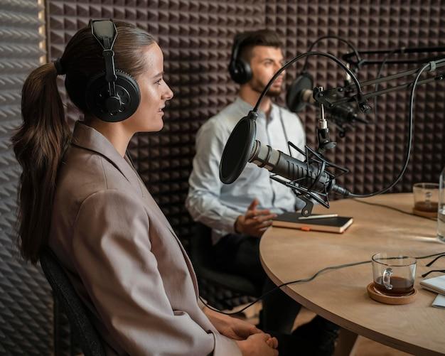 Hombre y mujer de tiro medio en la radio