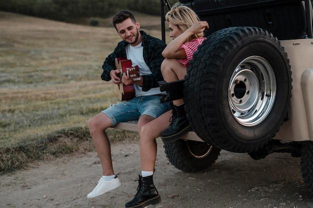 Hombre y mujer tocando la guitarra mientras viajan por care =