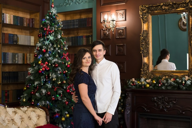 Hombre y mujer tomados de la mano cerca del árbol de navidad y la chimenea en el ambiente navideño.