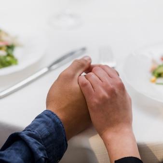 Hombre y mujer tomados de la mano de cerca