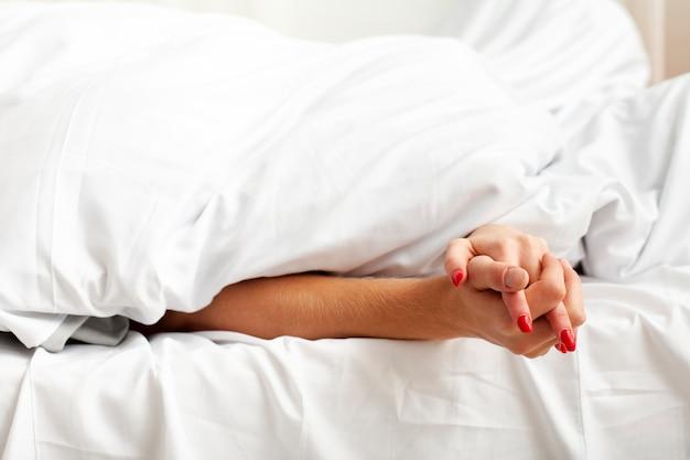 Hombre y mujer tomados de la mano detrás de las sábanas