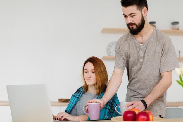 Hombre y mujer tomando café y usando la computadora portátil