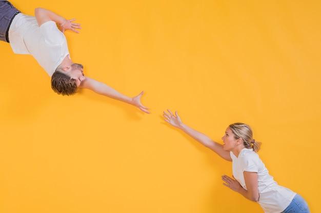 Hombre y mujer tratando de alcanzarse
