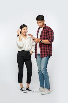 Hombre y mujer usan camisas y escuchan música en teléfonos inteligentes