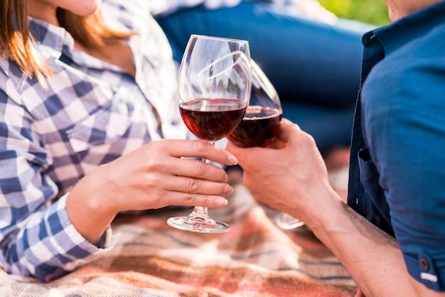 Hombre y mujer vasos tintineantes en picnic
