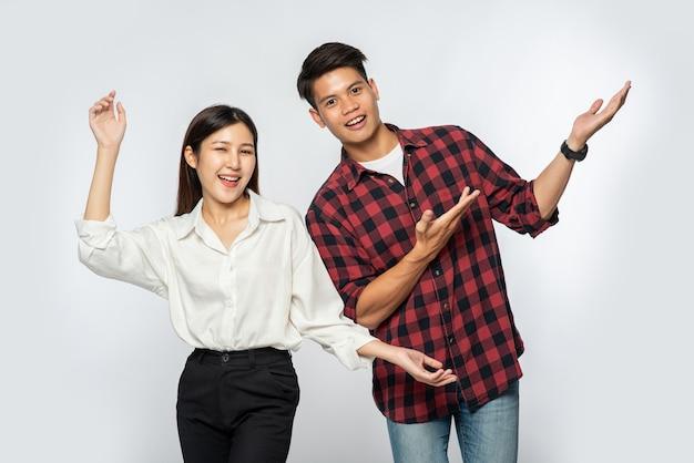 El hombre y la mujer vestían camisas y extendían felizmente sus manos hacia un lado