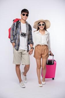 Hombre y mujer vestidos con gafas para viajar con maletas