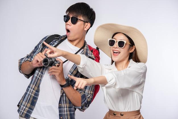 Hombre y mujer vestidos para viajar, usar gafas y tomar fotografías