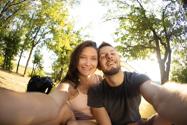 Un hombre y una mujer en un viaje de campamento se toman una selfie cerca de la tienda.