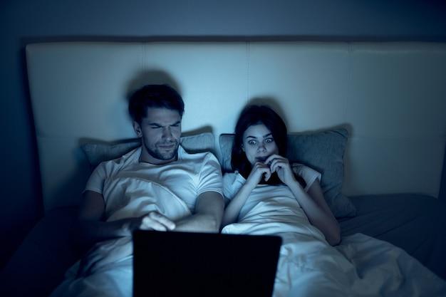 Un hombre y una mujer viendo películas por la noche en la cama.