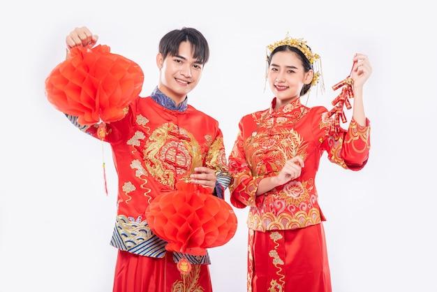 Hombre y mujer visten traje cheongsam celebran el año nuevo chino con lámpara roja y petardo