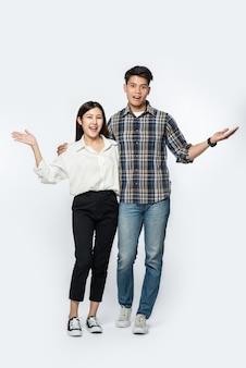 Hombre y mujer vistiendo camisas y felizmente extendieron sus manos hacia un lado.
