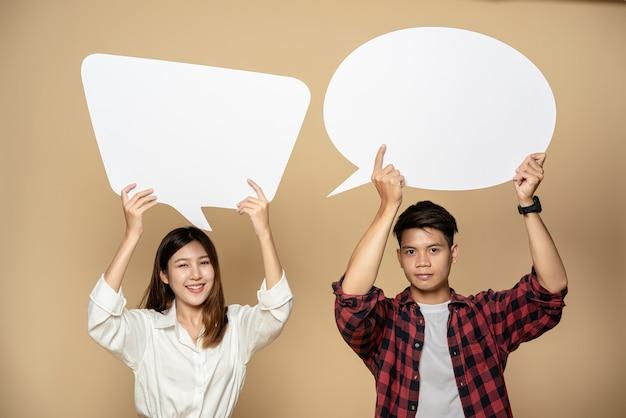 Hombre y mujer vistiendo camisetas y sosteniendo un símbolo de cuadro de pensamiento