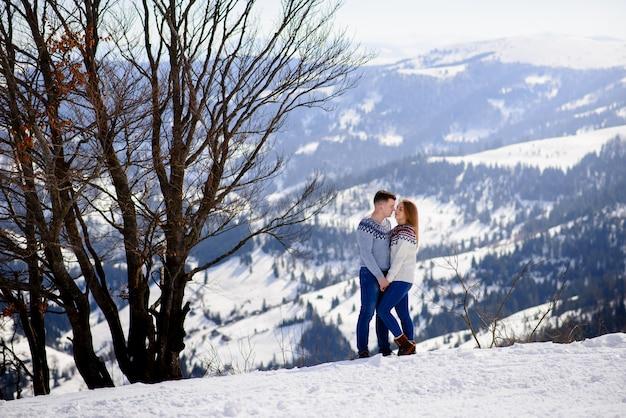 Hombre y mujer vistiendo ropa de punto besándose en la montaña nevada.