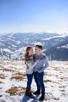 Hombre y mujer vistiendo ropa tejida abrazando en montaña nevada.