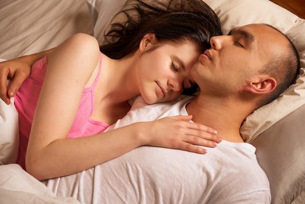 Un hombre y una mujer yacen en un abrazo en una cama