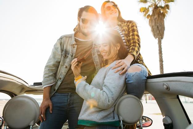 Hombre y mujeres alegres abrazándose e inclinándose fuera del auto