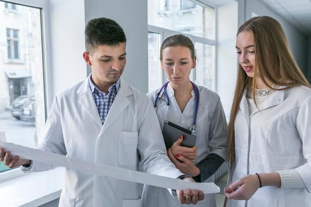 Hombre y mujeres doctores viendo cardiograma