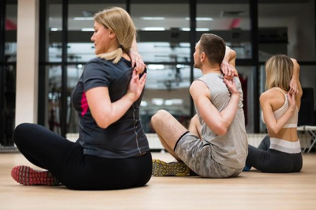 Hombre y mujeres estirando juntos en el gimnasio.