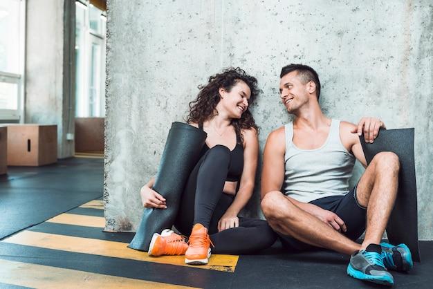 Hombre y mujeres felices con la estera del ejercicio que se sienta en gimnasio