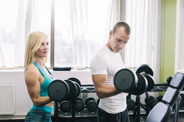 Hombre y mujeres levantando pesas