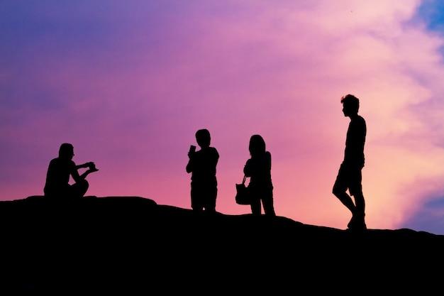 Hombre y mujeres silueta fotografía y selfie con la montaña al atardecer.