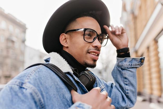 El hombre mulato inspirado viste una chaqueta de mezclilla informal caminando por la calle. foto al aire libre de chico africano con sombrero negro y gafas elegantes, pasar tiempo en la ciudad.