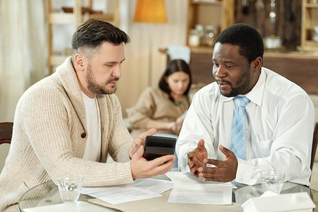 Hombre multiétnico adulto y consultor financiero sentado a la mesa con máquina de calcular mientras se habla de hipoteca