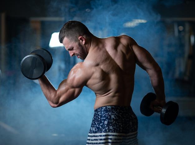 Hombre muscular joven que ejercita con pesas de gimnasia. guy entrena sus bíceps