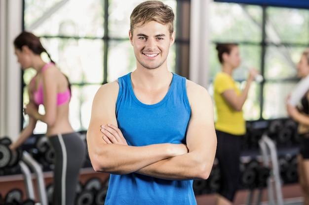 Hombre muscular que presenta con las mujeres atléticas detrás en el gimnasio
