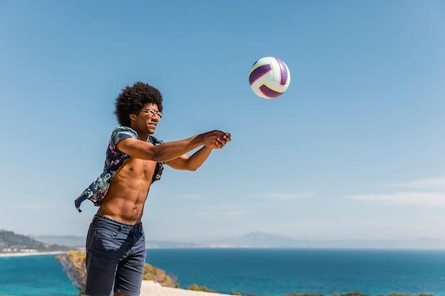 Hombre musculoso afroamericano saltando y sirviendo pelota