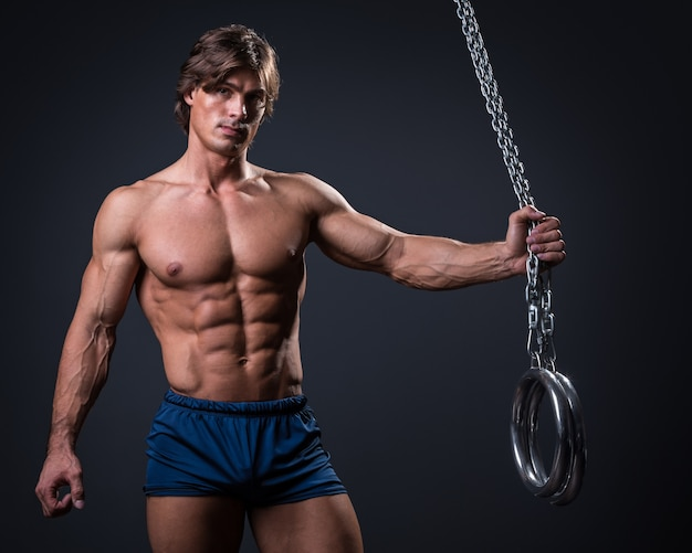Hombre musculoso y anillos metálicos