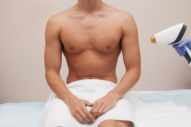 Hombre musculoso atleta con piel clara suave. depilación y depilación del cabello en salón de belleza. concepto de depilación láser masculino. esteticista utilizando aparatos modernos para procedimientos. cuidado de piel y belleza