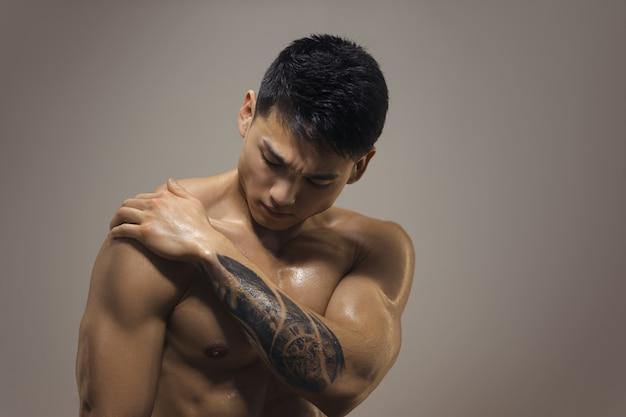 Hombre musculoso atlético que tiene dolor en las articulaciones del hombro.