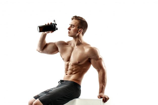 Hombre musculoso con bebida de proteína en agitador sobre fondo blanco.