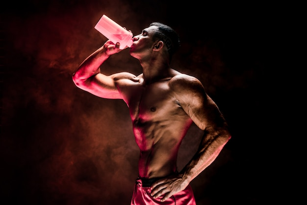 Hombre musculoso con bebida de proteína en agitador