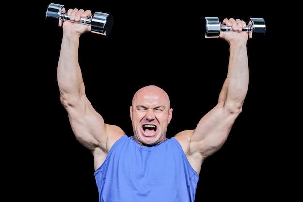 Hombre musculoso con los brazos levantados levantando pesas