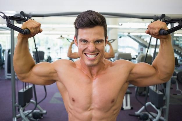 Hombre musculoso sin camisa con banda de resistencia en el gimnasio