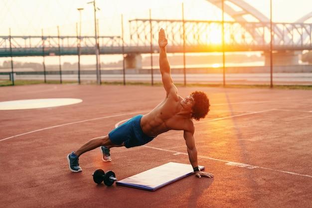 Hombre musculoso sin camisa haciendo ejercicios de estiramiento en la corte por la mañana.
