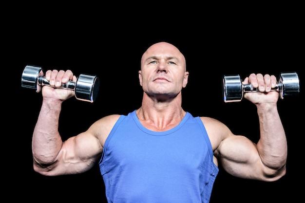 Hombre musculoso en chaleco levantando mancuernas