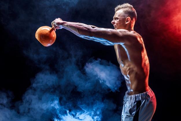 Hombre musculoso concentrado haciendo ejercicio con pesas rusas