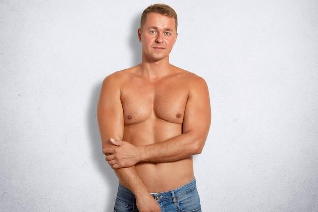 El hombre musculoso confiado que está en buena forma corporal, usa solo jeans, practica deporte regularmente, está aislado en un muro de concreto blanco, mantiene las manos parcialmente cruzadas. personas, concepto de estilo de vida saludable