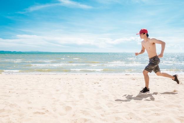 Hombre musculoso corre en la playa