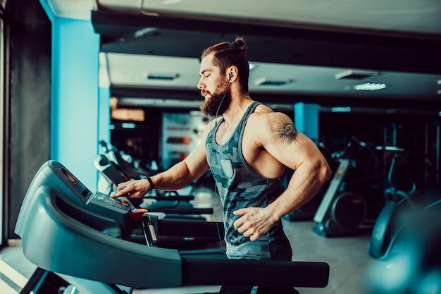 Hombre musculoso corriendo en la caminadora.