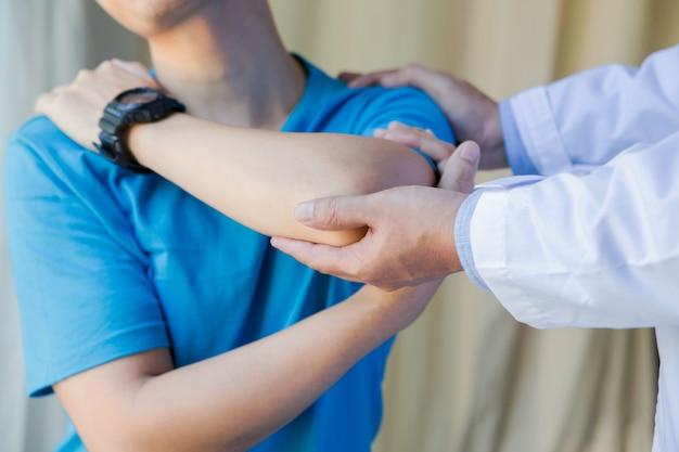Hombre musculoso con dolor de hombro haciendo ejercicio con fisioterapeuta