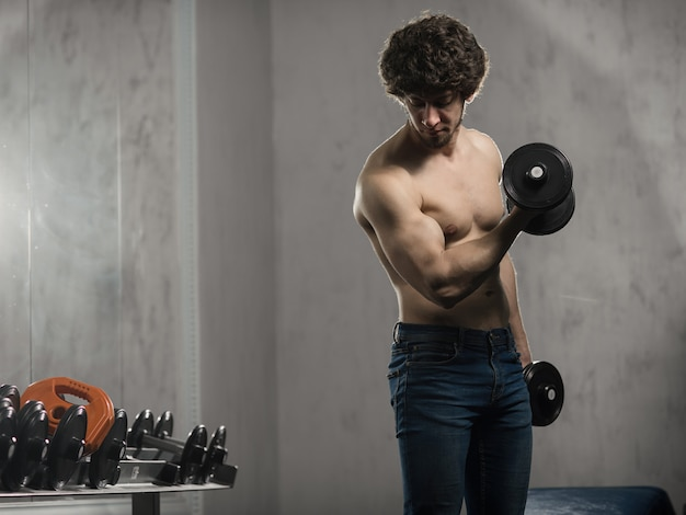 Hombre musculoso entrena pesas de bíceps en el gimnasio, entrenamiento manual