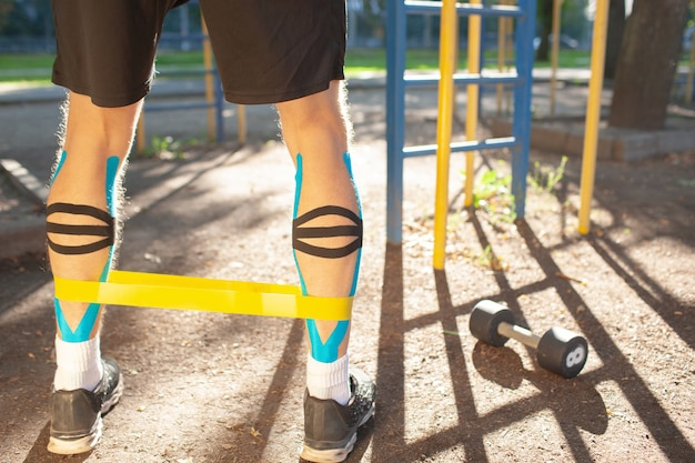 Hombre musculoso entrenamiento fitness banda de resistencia en las piernas en el campo de deportes